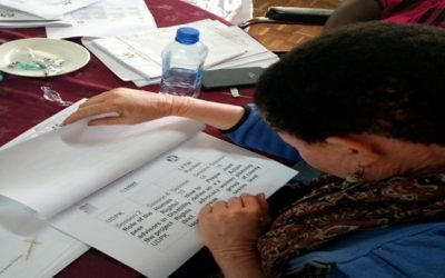 A-woman-with-visual-disability-going-through-large-font-training-materials-during-a-training-session-on-advocacy-640x480